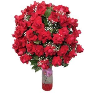 100 red roses in a vase with green plants