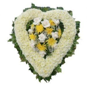Sympathy white heart arrangement with white and yellow flowers in the center
