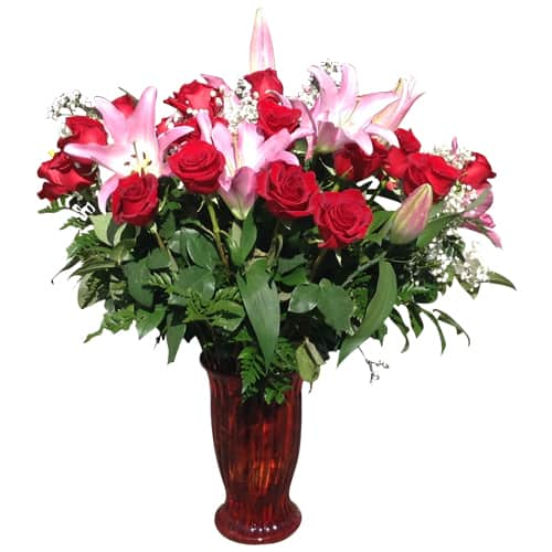 Vase with red roses, lilies and green plants