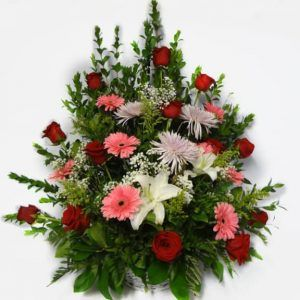 Bouquet in a basket with 12 Roses, 7 Gerberas Daisies, 3 Spiders, 2 while Lilies.
