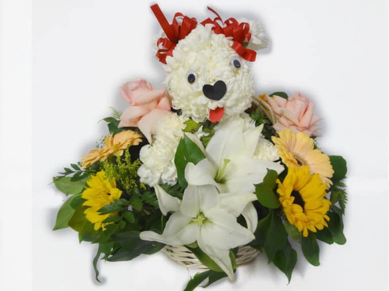 Basket bouquet with a white dog made it with flowers