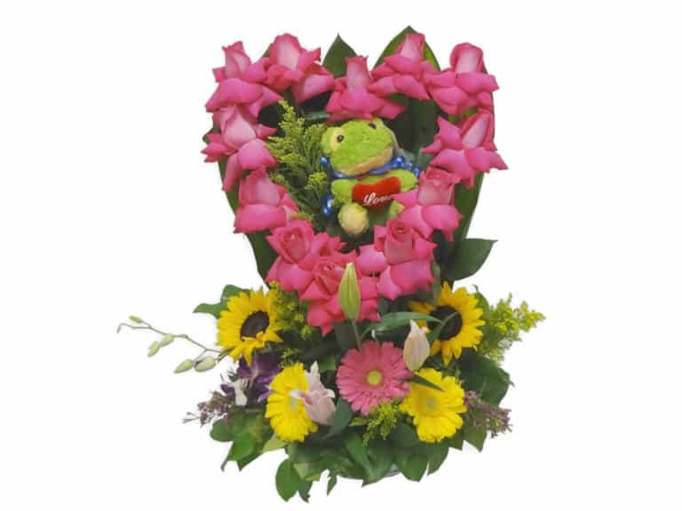 Green frog inside of a pink hearth of roses with 12 Roses, 2 Sunflowers, 3 Gerberas, 1 Orchid, 3 Lilies