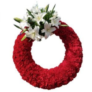 Sympathy arrangement with red carnations and white lilies in a circle